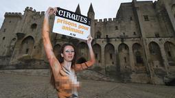 """Model asal Brasil, Juliana Marques menunjukkan plakat dengan tulisan """"Sirkus, penjara untuk binatang"""" saat melakukan aksi di Avignon, Prancis (11/2). Aksi model ini menjadi pusat perhatian warga setempat. (AFP Photo / Boris Horvat)"""