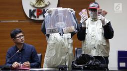 Wakil Ketua KPK, La Ode Muhammad Syarif (kiri) melihat barang bukti uang hasil OTT di Gedung KPK, Jakarta, Sabtu (26/6/2019). Dalam OTT tersebut, KPK menyita uang 20.874 dolar Singapura, 700 USD dan Rp 200 juta dari lima tersangka. (Liputan6.com/Helmi Fithriansyah)