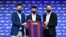 Penyerang baru Barcelona Pedri (tengah) berpose dengan jersey barunya di samping presiden klub Josep Maria Bartomeu (kiri) dan direktur olahraga Ramon Planes selama presentasi resminya di stadion Camp Nou di Barcelona (20/8/2020). Pemain 17 tahun itu diikat selama dua tahun. (AFP/Josep Lago)
