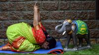 Instruktur dan juara yoga Kuchipudi Lakshmi  melakukan gerakan yoga menjelang Hari Yoga Internasional di lembaganya di Hyderabad, India pada 17 Juni 2020. Hari Yoga Internasional atau International Day of Yoga diperingati setiap tahun pada 21 Juni. (Photo by NOAH SEELAM / AFP)