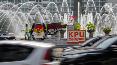Kendaraan melintas di dekat papan sosialisasi Pemilu 2019 di kawasan Bundaran HI, Jakarta, Rabu (3/4). KPU terus menyosialisasikan kepada masyarakat agar menggunakan hak pilihanya pada Pemilu 2019. (Liputan6.com/Faizal Fanani)