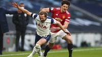 Striker Tottenham Hotspur Harry Kane diadang bek Manchester United atau MU dalam laga Liga Inggris di Tottenham Hotspur Stadium, Minggu (11/4/2021). (Clive Rose / Pool via AP)