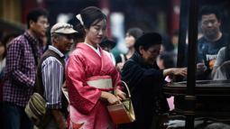 Gambar pada 21 Oktober 2019 menunjukkan seorang perempuan mengenakan pakaian tradisional Jepang, kimono, saat mengunjungi kuil Senso-ji di Tokyo. Sensoji Temple merupakan salah satu kuil tertua di Jepang yang terletak di Asakusa. (Anne-Christine POUJOULAT / AFP)