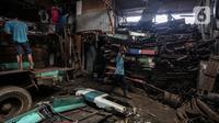 Pekerja membawa bagian Koperasi Angkutan Jakarta (Kopaja) yang telah dibongkar untuk diremajakan di kawasan Meruya, Jakarta Barat, Rabu (27/1/2021). Kopaja yang tak lagi digunakan tersebut dihancurkan untuk dijual secara kiloan ke penjual besi tua. (Liputan6.com/Johan Tallo)