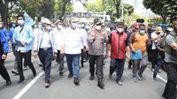 Presiden KSPSI Andi Gani Nena Wea dan Presiden KSPI Said Iqbal didampingi Kapolda Metro Jaya Irjen Pol Fadil Imran berjalan kaki menuju Mahkamah Konstitusi (MK) untuk menyerahkan Petisi May Day.