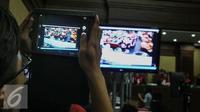 Pengunjung sidang mengabadikan rekaman CCTV dalam persidangan saksi kasus pembunuhan Wayan Mirna Salihin di PN Jakarta Pusat, Rabu (13/7). Sidang menampilkan video CCTV yang berisi rekaman kejadian di Kafe Olivier. (Liputan6.com/Faizal Fanani)