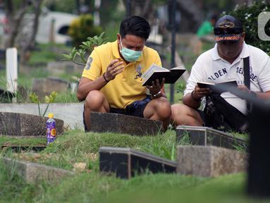Peziarah membaca doa di salah satu makam di Tempat Pemakaman Umum Karet Bivak, Jakarta, Sabtu (18/4/2020). Selama masa PSBB, peziarah yang memasuki kawasan TPU dibatasi dan diwajibkan menggunakan masker sebagai langkah pencegahan penyebaran virus Covid-19. (Liputan6.com/Helmi Fithriansyah)