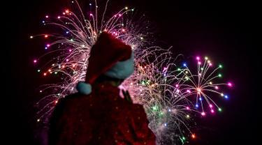 Seorang pria mengenakan kostum santa melihat kembang api selama parade Natal di Panama City (16/12). Warga Panama tengah mempersiapkan diri menyambut datangnya Natal 2018 yang jatuh pada tanggal 25 Desember. (AFP Photo/Luis Acosta)