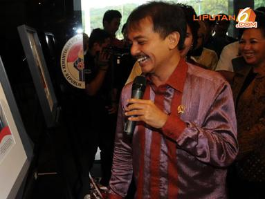 Roy Suryo melihat foto-foto yang mendokumentasikan kegiatannya selama setahun menjabat sebagai Menpora (Liputan6.com/Helmi Fithriansyah).