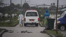 Sebuah mobil van membawa jenazah korban virus Corona Covid-19 untuk dimakamkan di tengah hujan lebat di pemakaman Keputih, Surabaya (7/1/2020). Pemerintah Kota Surabaya menyediakan tempat di TPU Keputih dan TPU Babat Jerawat untuk lahan pemakaman korban Covid-19. (AFP/Juni Kriswanto)