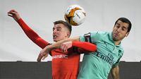 Gelandang Arsenal, Henrikh Mkhitaryan berebut bola dengan gelandang Rennes, Benjamin Bourigeaud selama pertandingan leg pertama babak 16 besar Liga Europa di Roazhon Park Prancis (7/3). Rennes menang telak 3-1. (AFP Photo/Loic Venance)