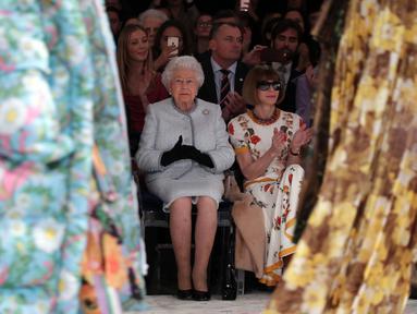 Ratu Elizabeth II duduk di sebelah Ratu Fashion, Anna Wintour menyaksikan pagelaran London Fashion Week 2018, Selasa (20/2). Ratu Elizabeth tampil stylish mengenakan setelan jaket dan rok biru muda keluaran Angela Kelly. (Yui Mok/Pool photo via AP)