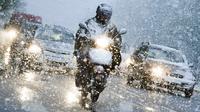 Pengendara motor melintasi hujan salju di Munich, Jerman selatan, (18/4). Hujan salju yang melanda kawasan ini tidak menyurutkan warga untuk tetap beraktivitas. (AFP PHOTO / dpa / Tobias Hase / Jerman OUT)