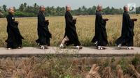 Para Bikkhu berjalan melewati area persawahan menuju Candi Blandongan saat melaksanakan prosesi Puja Waisak 2561 BE di komplek Candi Jiwa, Batujaya, Karawang, Jawa Barat (21/5). (Liputan6.com/Gempur M Surya)