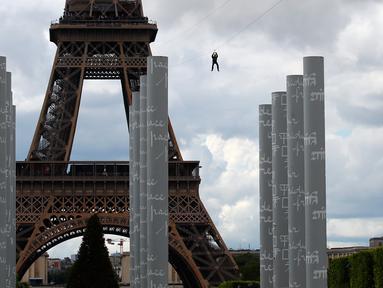 Pengunjung meluncur dengan seutas tali saat melakukan permainan Zip Line dari lantai dua Menara Eiffel di atas taman Champ de Mars, Paris, Selasa (28/5/2019). Kegiatan yang mirip dengan flying fox ini dipasangkan di atas ketinggian 115 meter dengan kecepatan 30 km per jam. (AP/Francois Mori)
