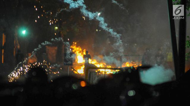 Polisi menembakan gas air mata ke arah massa di kawasan Tanah Abang, Jakarta Pusat, Rabu (22/5/2019). Massa terus melakukan perlawanan pasca buntut dari unjuk rasa hasil penghitungan suara Pemilu 2019 di depan kantor Bawaslu. (Liputan6.com/Herman Zakharia)
