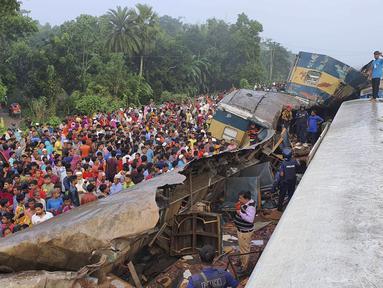 Orang-orang berkumpul di dekat gerbong kereta yang rusak parah setelah dua kereta yang melaju bertabrakan di distrik Brahmanbaria, 82 kilometer (51 mil) timur ibukota, Dhaka, Bangladesh, Selasa (12/11/2019). Sekitar 16 orang tewas dan 60 lainnya terluka akibat kecelakaan tersebut. (AP Photo)