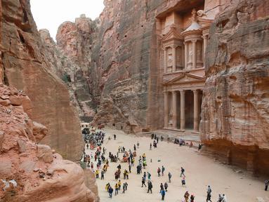 Wisatawan jalan-jalan saat mengunjungi kota arkeologi Petra, Yordania, Kamis (21/11/2019). Petra ditetapkan sebagai salah satu dari Tujuh Keajaiban Dunia Baru oleh Yayasan New7Wonders pada tahun 2017. (AHMAD ABDO/AFP)