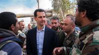 Presiden Suriah Bashar al-Assad berbincang dengan pasukan pemerintah di garis depan wilayah Ghouta Timur, Minggu (18/3). Ini adalah pertama kalinya Assad mengunjungi daerah ini selama bertahun-tahun. (HO/SYRIAN PRESIDENCY FACEBOOK PAGE/AFP)