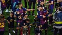 Luis Suarez dan Lionel Messi merayakan gelar La Liga 2018-2019 di Camp Nou bersama buah hati mereka, Minggu dini hari WIB (28/4/2019). (AFP/Lluis Gene)