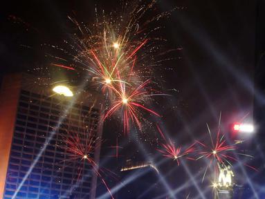 Nyala kembang api memeriahkan suasana malam pergantian tahun di kawasan Bundaran Hotel Indonesia, Jakarta, Selasa (31/12/2019). Ribuan masyarakat melewati malam pergantian tahun 2019 menuju 2020 dengan menyalakan kembang api dan menikmati panggung hiburan. (Liputan6.com/Angga Yuniar)