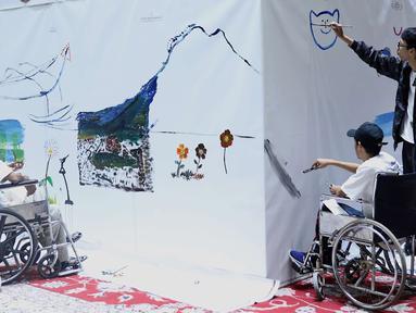 Penyandang disabilitas melukis mural di kanvas sepanjang 20 meter di Balai Kota DKI Jakarta, Kamis (11/10). Kegiatan tersebut diadakan sebagai sarana untuk para penyandang disabilitas berkarya. (Liputan6.com/Immanuel Antonius)