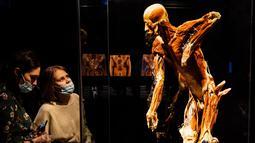 Pengunjung melihat salah satu karya seni yang dipajang dalam pameran anatomi tubuh manusia bertajuk 'Body Worlds' di Moskow, Rusia (24/3/2021). Pameran ini menjadi polemik dan menuai banyak kecaman lantaran menggunakan mayat manusia. (AFP/Dimitar Dilkoff)