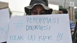 Massa yang tergabung dalam Koalisi Masyarakat Menyelamatkan KPK membentangkan poster saat aksi menolak UU KPK di Gedung DPR, Jakarta, Selasa (17/9/2019). Dalam aksinya massa membawa poster bertuliskan kekecewaan terhadap Jokowi dan DPR karena mengesahkan UU KPK. (merdeka.com/Iqbal S. Nugroho)