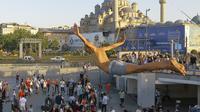 Seorang pria menyelam ke perairan Tanduk Emas dengan latar belakang Yeni Cami, di Istanbul, Selasa (27/7/2021). Turki telah mencatat lebih dari 15.000 kasus virus corona baru, karena jumlah infeksi yang terus meningkat. (AP Photo/Mucahid Yapici)