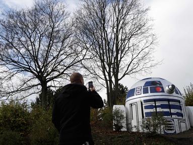 Seorang pria memotret ventilasi bunker nuklir yang dicat oleh ulah kreatif seniman jalanan sehingga menyerupai robot R2-D2 di film Star Wars di sebuah taman di Praha, Republik Ceko, (28/10). (AP Photo/Petr David Josek)