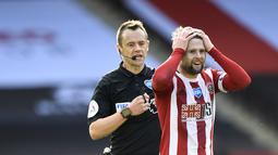 Pemain Sheffield United Oliver Norwood (kanan) mendapat kartu kuning dari wasit Stuart Attwell (tengah) usai melanggar pemain Everton Richarlison pada pertandingan Premier League di Bramall Lane, Sheffield, Inggris, Senin (20/7/2020). Everton menang 1-0. (AP Photo/Peter Powell, Pool)
