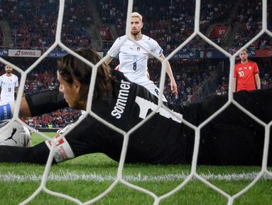 Kiper Swiss, Yann Sommer tampil cemerlang saat menahan Italia 0-0 dalam laga Kualifikasi Piala Dunia 2022 Grup C Zona Eropa di St Jakob-Park Stadium, Basel, Minggu (5/9/2021). Sejumlah peluang Italia berhasil dipatahkan termasuk eksekusi penalti Jorginho. (Foto: AFP/Fabrice Coffrini)