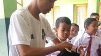 Para siswa SDN 1 Bayongbong, Garut nampak asik saat pelaksanaan cukur rambut gratis saat Hari Anak Sedunia (Liputan6.com/Jayadi Supriadin)