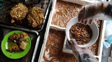 Pedagang membuat kuliner cha ruoi di sebuah warung di Hanoi, Vietnam, Jumat (14/12). Cha ruoi merupakan kue hangat berbentuk dadar yang terbuat dari campuran daging babi, telur, daun dill, kulit jeruk, dan segenggam cacing goreng. (Manan Vatsyayana/AFP)