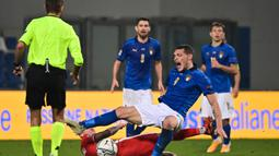 Gelandang Polandia, Jacek Goralski (bawah), menjatuhkan striker Italia, Andrea Belotti dalam laga UEFA Nations League Grup A1 di Stadion Mapei, Italia, Senin (16/11/2020) dini hari WIB. Polandia kalah 0-2 dari Italia. (AFP/Miguel Medina)
