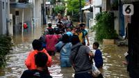 Warga melewati banjir yang menggenangi kawasan Kampung Pulo, Jakarta, Kamis (2/1/2020). Hujan yang terjadi kemarin malam membuat Kali Ciliwung meluap ke jalan. (merdeka.com/Imam Buhori)