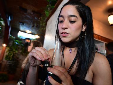 Erika Soto memegang alat oleskan dari Puffco sehari sebelum pembukaan resminya di Lowell Cafe di Hollywood Barat, California  (30/9/2019). Kafe ganja pertama di Amerika telah dibuka di Hollywood Barat. (AFP Photo/Frederic J. Brown)