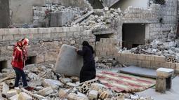 Keluarga Tareq Abu Ziad bersiap untuk berbuka puasa di tengah reruntuhan rumah mereka yang hancur setelah serangan militer pasukan pemerintah dan sekutunya di Kota Ariha, Provinsi Idlib, Suriah, Senin (4/5/2020). Muslim Suriah melewati Ramadan tahun ini masih dalam kondisi perang. (AAREF WATAD/AFP)