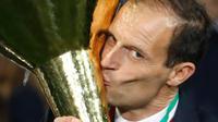 Pelatih Juventus, Massimiliano Allegri mencium Piala Liga Italia Serie A usai menjuarainya untuk ke-33 kalinya di Stadion Allianz, Turin (19/5/2019). Juventus meraih gelar scudetto kedelapan secara beruntun sekaligus rekor baru. (AP Photo/Antonio Calanni)