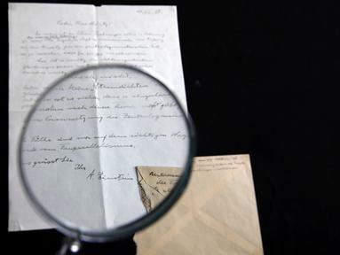 """Petugas rumah lelang Winner melihat surat yang ditulis tangan Albert Einstein mengenai rumusan """"Tahap Ketiga Teori Relativitas"""" dengan kaca pembesar di Yerusalem, Selasa (6/3). Surat itu dibeli dengan harga sekitar Rp 1,2 miliar. (MENAHEM KAHANA/AFP)"""