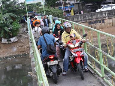 Warga serta pengendara motor menyeberangi Kanal Banjir Barat (KBB) di kawasan Tanah Abang, Jakarta, Jumat (30/12). Tidak tersedianya fasilitas penyeberangan lain membuat warga serta pengendara harus berbagi jalan. (Liputan6.com/Immanuel Antonius)