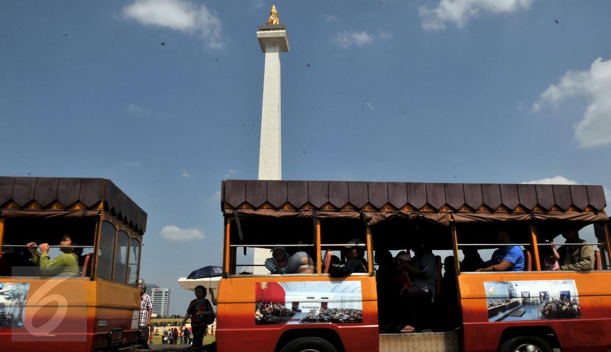 Monumen Nasional atau Monas masih menjadi tempat favorit wisata warga untuk berlibur, Jakarta, Minggu (19/7/2015). Ikon kota Jakarta tersebut menjadi tempat wisata alternatif warga saat liburan lebaran. (Liputan6.com/Johan Tallo)