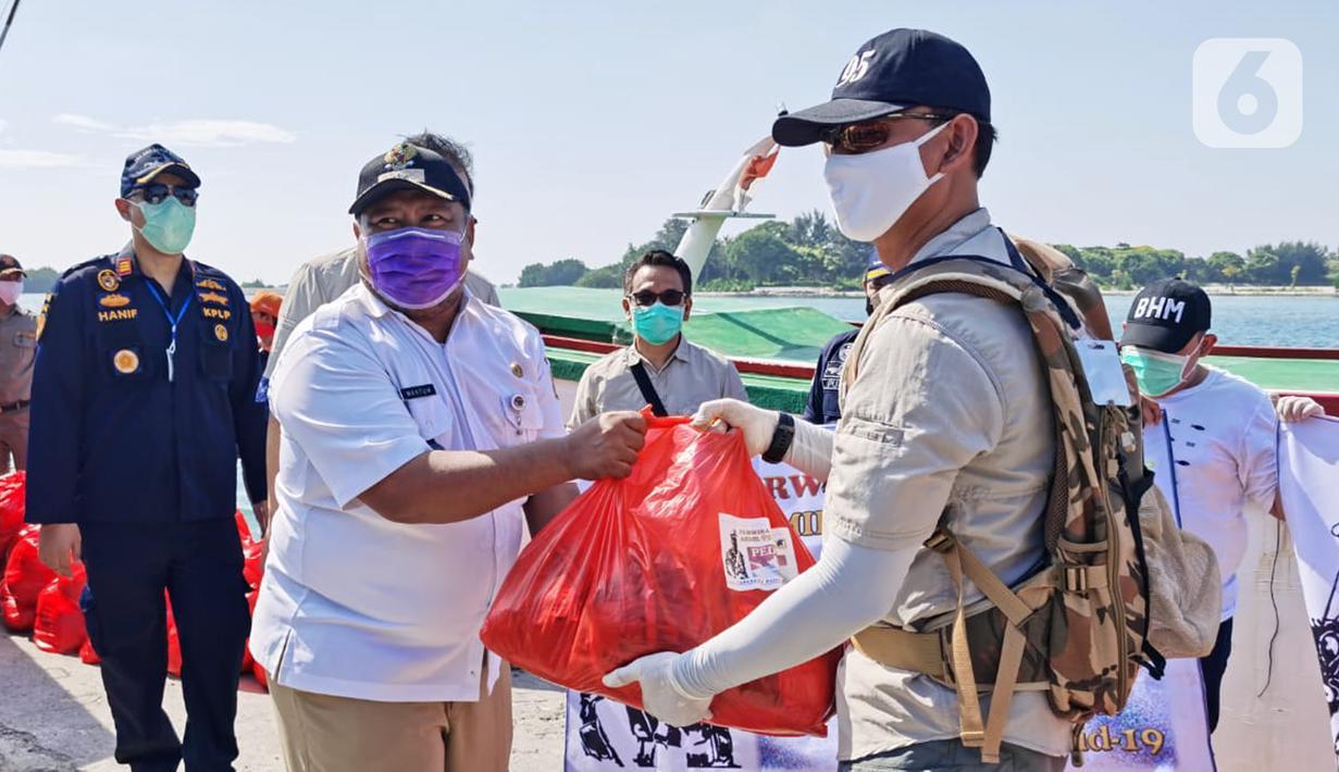 Ketua Paguyuban Perwira Abituren Akmil 95 Kolonel Inf Sumirating Baskoro secara simbolis memberikan donasi kepada Lurah Pulau Pari, Mahtum di Pulau Pari, Rabu (20/5/2020). Donasi berupa 2000 paket Sembako,200 set APD, 1000 masker medis dan 50 pasang sarung tangan. (Liputan6.com/Pool/Damadika 95)