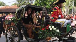Presiden Jokowi dan Ibu Negara, Iriana berada di kereta kencana menuju Graha Saba Buana, Solo, Rabu (8/11). Pernikahan putri presiden Jokowi, Kahiyang Ayu dengan Bobby Nasution diiringi prosesi kirab kereta kencana. (Liputan6.com/Angga Yuniar)
