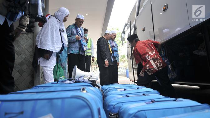 Panitia Penyelenggara Ibadah Haji (PPIH) membantu memindahkan koper milik jemaah haji kloter 2 saat tiba di Asrama Haji Pondok Gede, Rabu (29/8). (Merdeka.com/Iqbal S. Nugroho)