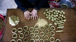 Kesibukan anggota keluarga Palestina menyiapkan kue-kue tradisional untuk dijual sebagai persiapan liburan Idul Fitri mendatang, di kota Rafah, Jalur Gaza, Selasa (4/5/2021). Pembuatan kue tradisional untuk Hari Raya Idul Fitri atau Lebaran yang menandai akhir bulan Ramadhan. (KATA KHATIB/AFP)