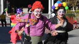 Para peserta berkostum badut berlarian selama acara 'Running of the Clowns' di Pasadena, California pada 21 Oktober 2018. Lari dikejar kawanan badut ini merupakan parodi yang mengolok-olok lomba dikejar banteng di Pamplona, Spanyol. (Mark RALSTON/AFP)