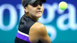 Petenis Kanada, Bianca Andreescu mengembalikan bola ke arah petenis Swiss, Belinda Bencic pada babak semifinal AS Terbuka di Arthur Ashe Stadium, Kamis (6/9/2019). Petenis berusia 19 tahun itu mengamankan tiket ke final usai menang dengan skor 7-6 (7-3) dan 7-5. (Clive Brunskill/Getty Images/AFP)