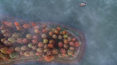 Warga mengendarai perahu di Danau Tianquan yang berselimut kabut di Xuyi di Provinsi Jiangsu, China (20/11/2019). Memasuki musik dingin, pemandangan Danau Tianquan berselimut kabut tipis berpadu dengan pepohonan berdaun kemerahan terlihat lebih indah dari biasanya. (AFP Photo/Str)