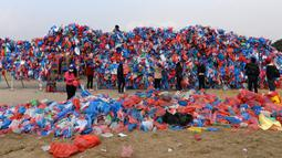 Relawan Nepal dan siswa sekolah membuat replika Laut Mati dari plastik daur ulang di Kathmandu pada 5 Desember 2018. Sebanyak 100.000 kantong plastik diikat di atas kisi besi dengan lebar 20 meter dan tinggi 5 meter. (PRAKASH MATHEMA / AFP)